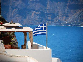 דגל יוון על רקע נוף האי סנטוריני