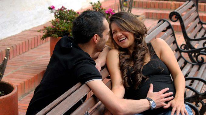 גבר מניח את ידו על בטנה של אישה בהריון
